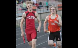 Harlan Community's Ben Renkly (left) passes Carroll's anchor runner in the final 20 meters to earn first place for the Cyclone medley relay team at Thursday's Tiger-Knight Co-Ed Relays.
