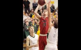 Cyclone senior Shane Chamberlain scores two of his 15 points over Tyler Blaha of St. Albert. (Photos by Mike Oeffner)