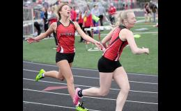 HCHS seniors Sidney Craig (left) and Cassidy Riley make the first exchange in the 4x200 relay during Thursday's Koos Invitational. Ashley Hall and Alyssa Sotelo ran the final two legs of the event and earned second place for the Cyclones. (Photos by Mike Oeffner)