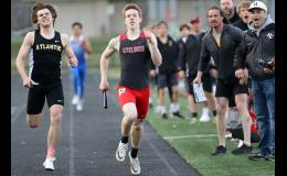 Harlan Community sophomore Michael Erlemeier (right) nears the finish line in the 4x400 relay with Atlantic's Chase Mullenix in hot pursuit. Erlemeier held off the challenge of Mullenix to secure the Cyclones' only gold medal of the night and also clinch the team title for HCHS in Tuesday's Ken Carstens Invitational at Merrill Field. (Photos by Mike Oeffner)