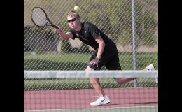HCHS senior Nolan Heese makes a running forehand return shot from behind the baseline during his singles win vs. Red Oak.