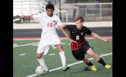 HCHS junior Rolly Lokange (10) fights off Panther sophomore Dale Boyer for possession. Lokange scored his first varsity goal in the second half. (Photos by Mike Oeffner)