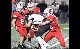 HCHS senior defensive end Jake McLaughlin (83) tackles Glenwood quarterback Zach Carr for one of his two second-half sacks as teammates Allen Fries (55) and Caleb Bieker also rush the passer. The Cyclones sacked Carr eight times during the course of Friday's 42-12 Homecoming win at Merrill Field.