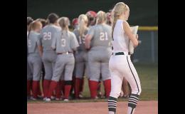 IKM-M senior Payton Sporrer carries the second base bag off the field for the final time following Monday's 9-3 regional final loss to Earlham, which huddles in shallow right field.