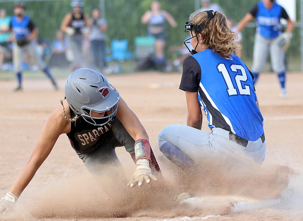 Exira-EHK's Alisa Partridge slides safely into third base in the bottom of the seventh inning as Griswold's Brenna Rossell (12) takes the throw.