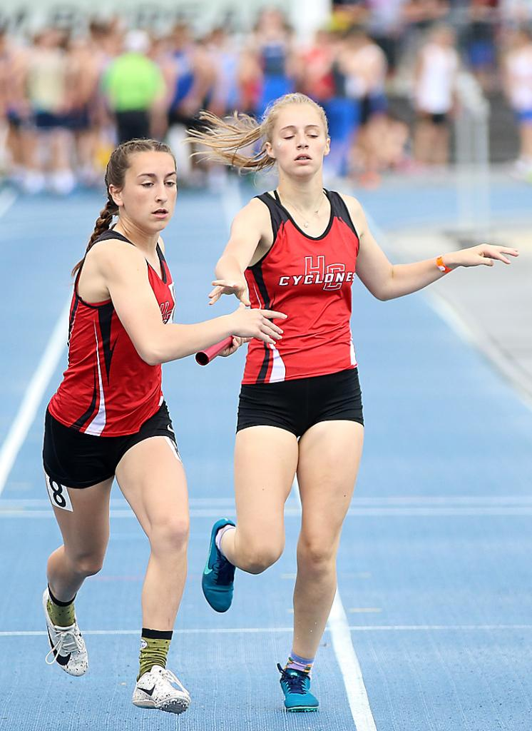 Cyclone senior Abby Alberti (left) takes a handoff from Lilly Metzger in the Class 3A 4x400 relay prelims at last year's state track meet. The versatile Alberti competed on four Cyclone relays at state, running a 100, 200, 400 and 800.