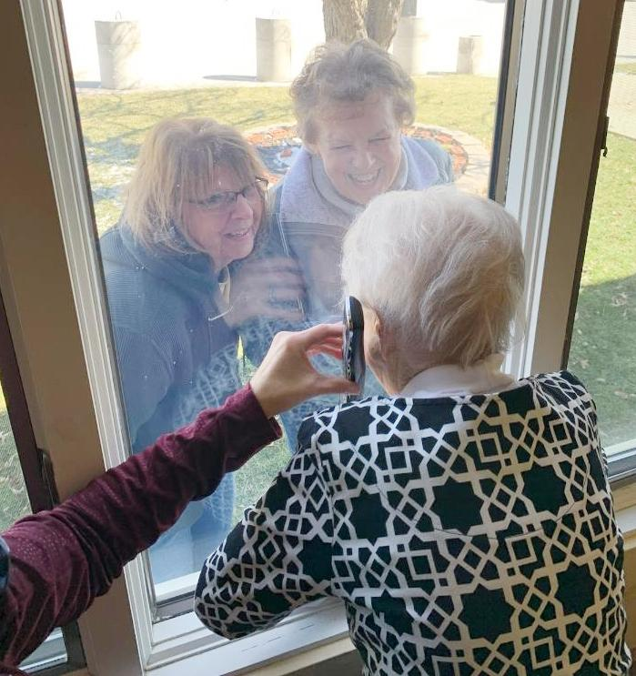 Elm Crest Retirement Community has implemented strict measures for the safety of its residents. Here,  Arlene Adams talks with her daughters, Cindy and Penny, through the window.  (Photo contributed)