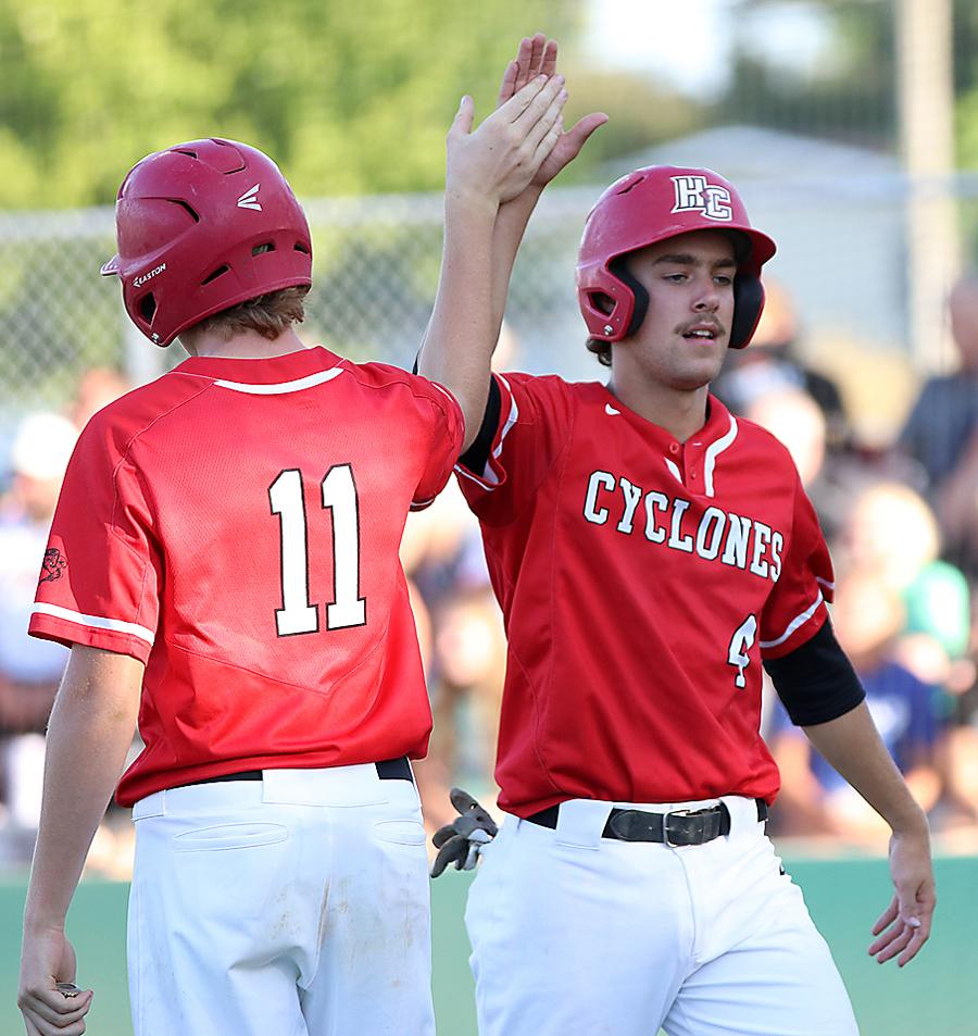 HCHS senior Brett Sears (right) slaps five with Isaiah Ahrenholtz after scoring the Cyclones' only run vs. ADM on a wild pitch in the first inning.