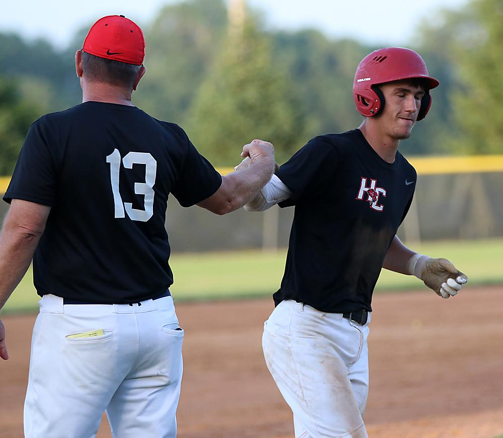 HCHS junior Brenden Bartley (right) is greeted by head coach Steve Daeges as he rounds third base after hitting a two-run homer during Friday's district semifinal win over Creston. Bartley also doubled and went 3-for-3 with three RBI in the Cyclones' 9-2 victory. (Photos by Mike Oeffner)