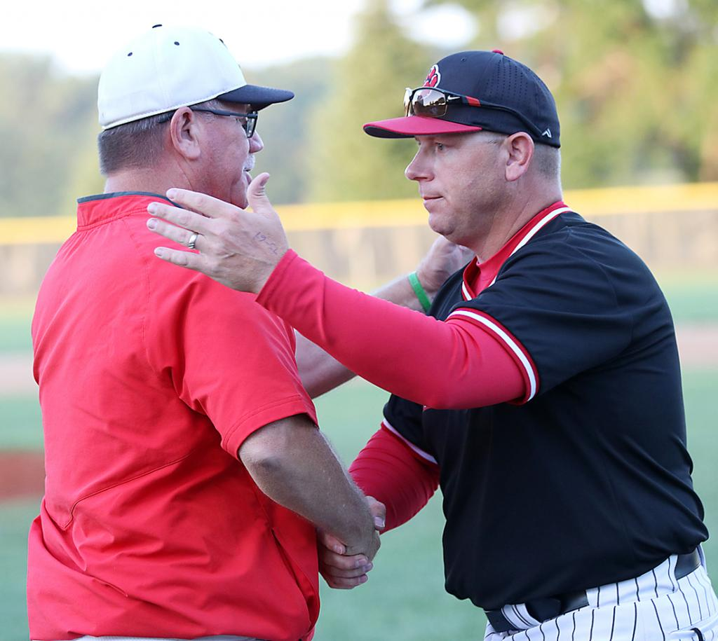 ADM coach Jason Book (right), a Walnut native, is congratulated by HCHS coach Steve Daeges after the Tigers defeated the Cyclones 3-1 in Wednesday's Class 3A, Substate 8 final. HCHS finished the season 26-8 overall.