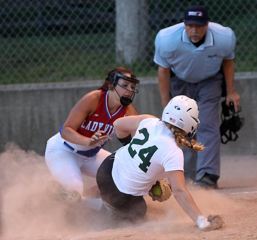 IKM-Manning senior Lexi Branning (24) scores on a wild pitch, sliding under the tag of AHSTW pitcher Madison Thornton.