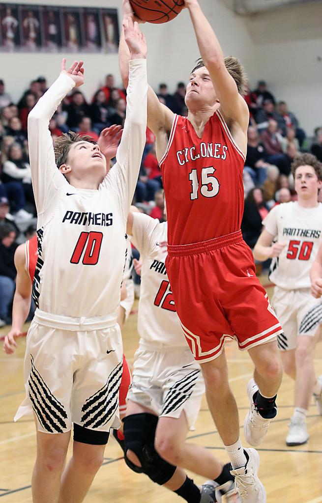 Cyclone senior Connor Bruck (15) drives at Creston's Colby Burg.
