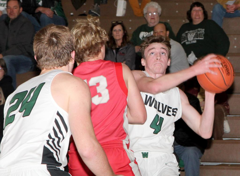 IKM-Manning senior Colby Keller (4) attacks the basket against Audubon Monday night as teammate Colten Brandt looks on. Keller led the Wolves to victory with 14 points and six assists. (Photos by Kim Wegener)