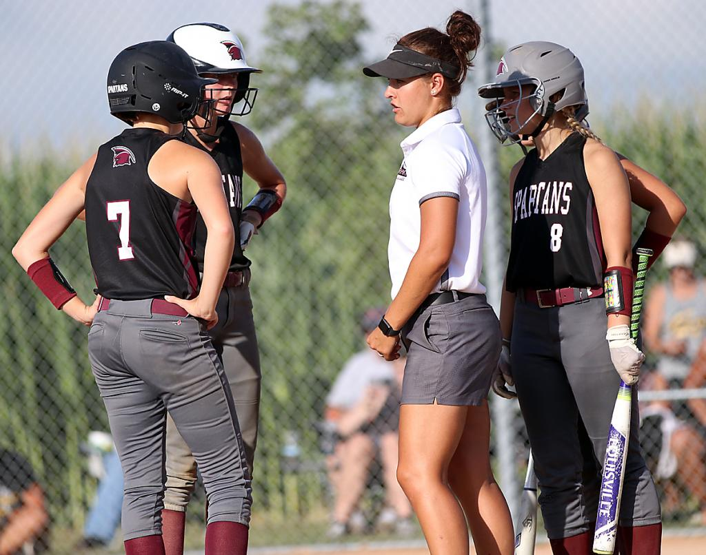 First-year Exira-EHK softball coach Andrea Nulle talks with her players, including Kate Hansen (7) and Alisa Partridge (8) during last week's regional semifinal win over West Harrison. The Spartans finished the 2020 season with a record of 15-1. (File photo)