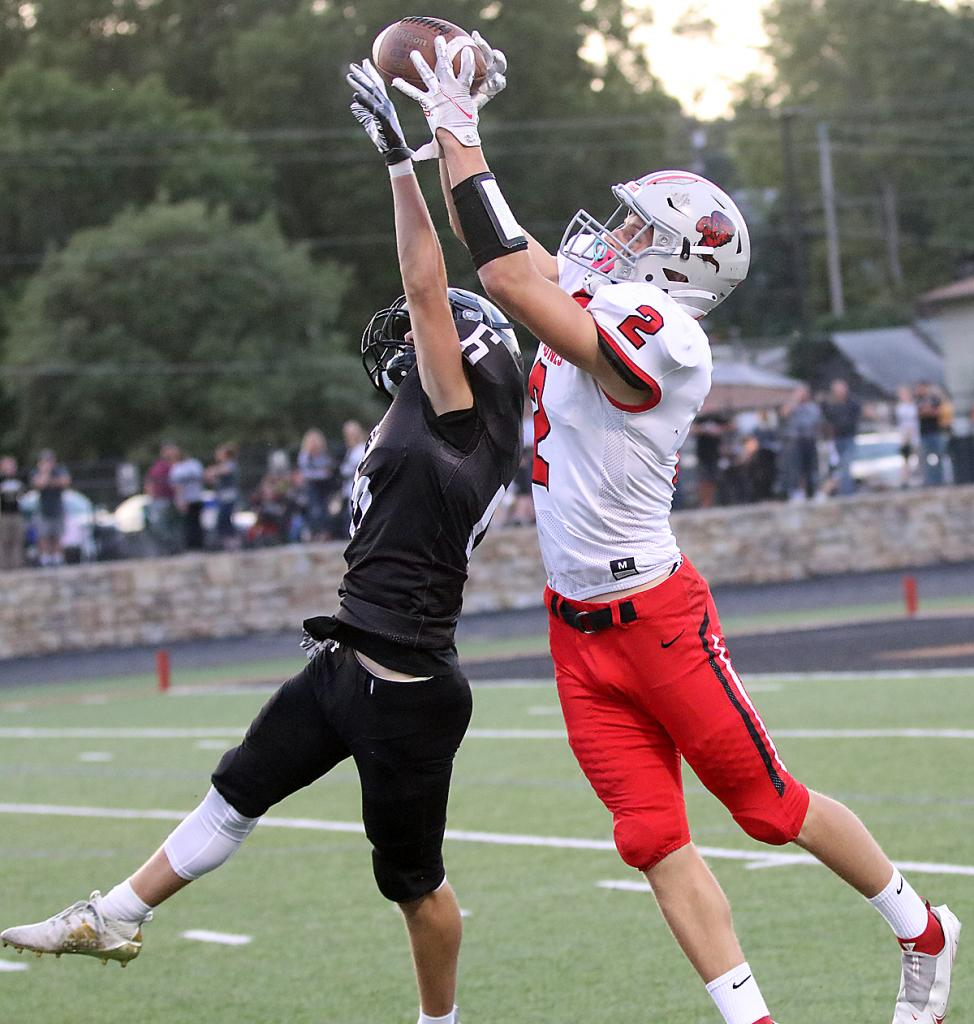 HCHS senior Connor Frame (2) jumps over Glenwood's Tommy Johnson to catch a first-quarter pass from Teagon Kasperbauer. Frame ran to the end zone to complete a 33-yard touchdown reception and finished with 115 receiving yards as the top-ranked Cyclones improved to 4-0 with a 41-13 win. (Photos by Mike Oeffner)