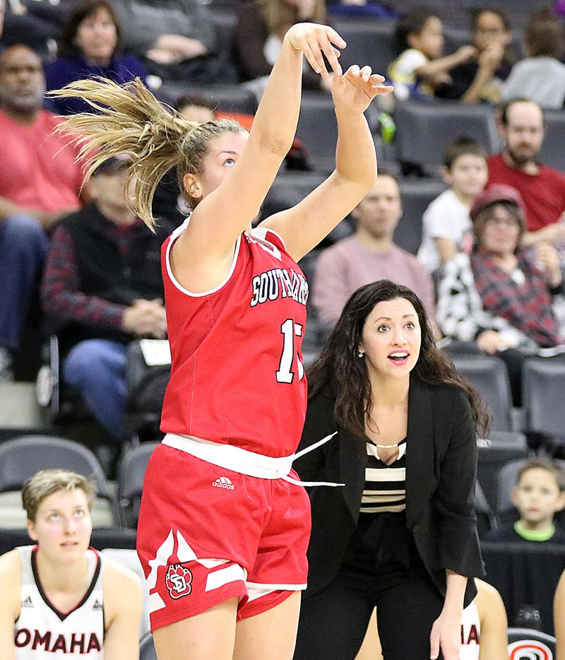 South Dakota's Taylor Frederick shoots a three-pointer in front of the UNO bench and Mavericks' coach Brittany Lange during a January 20 game. Frederick finished with 12 points and five rebounds in USD's 80-49 victory.