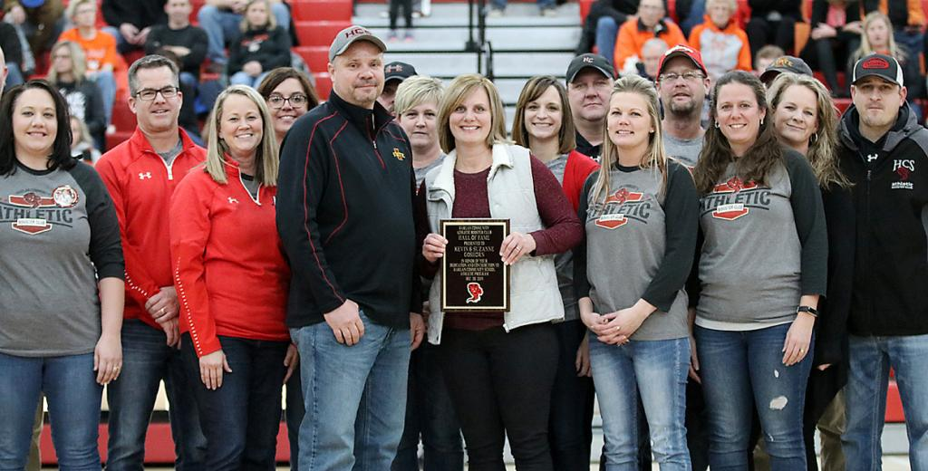 Kevin and Suzanne Goshorn (center) were presented with a Hall of Fame plaque by booster club president Josh and EJ Leinen and also joined on the floor by fellow booster club board members.