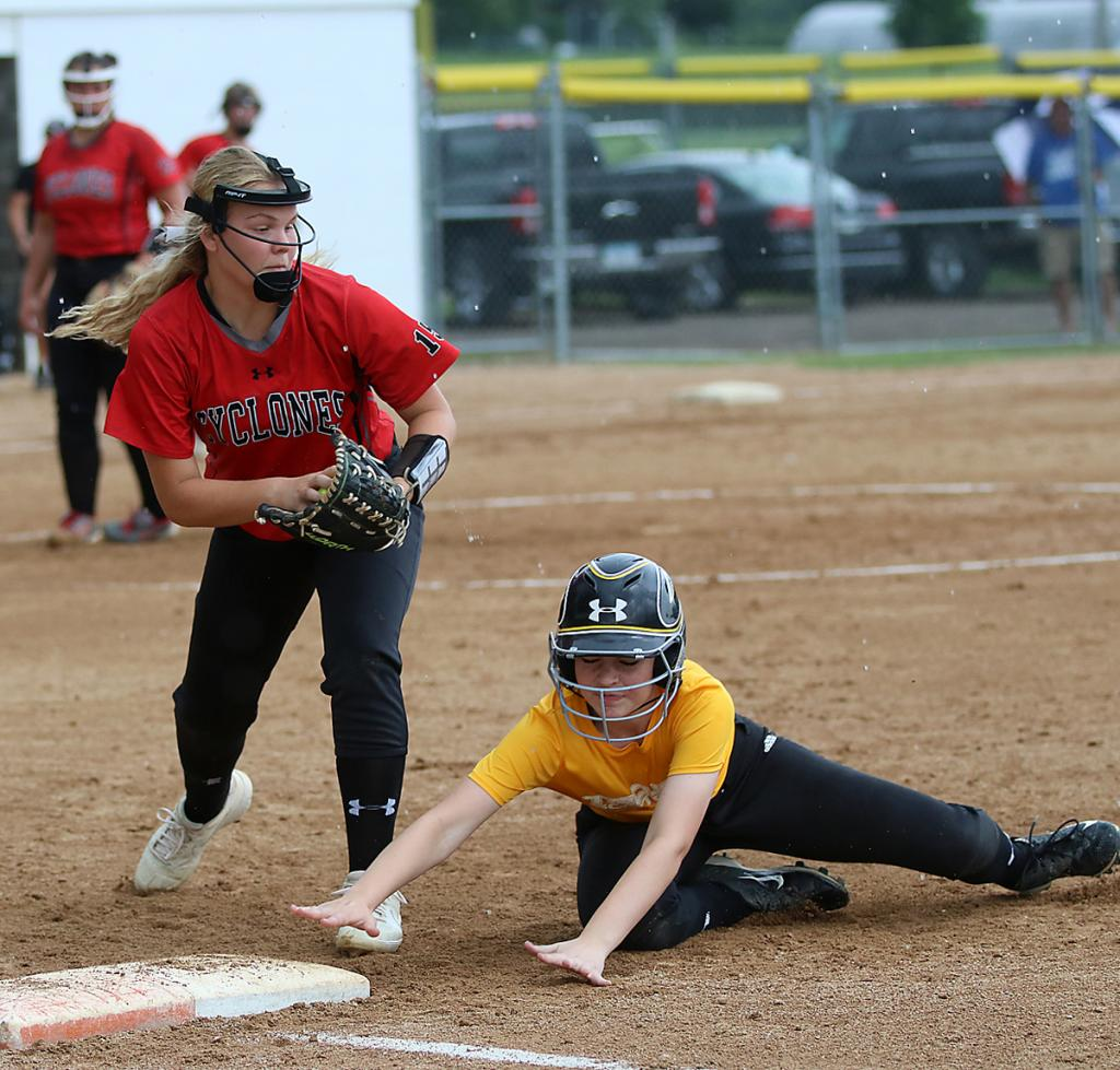 As the raindrops start to fall, a Tri-Center runner dives back to first base as HCHS freshman Jordan Heese looks to apply the tag on a pickoff attempt.