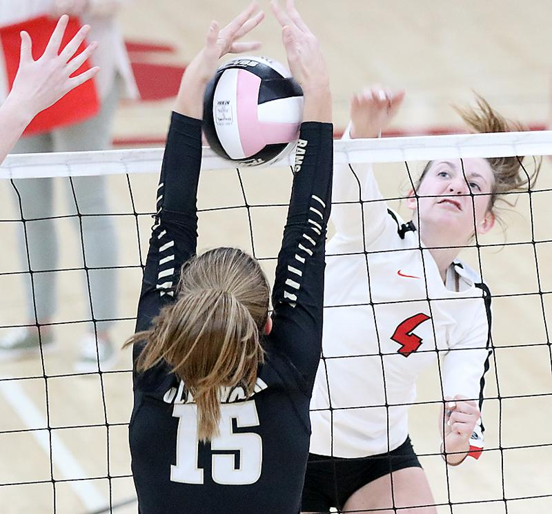 HCHS sophomore Zophi Hendricks splits the uprights with a kill through the hands of Glenwood's Taryn Bertini.
