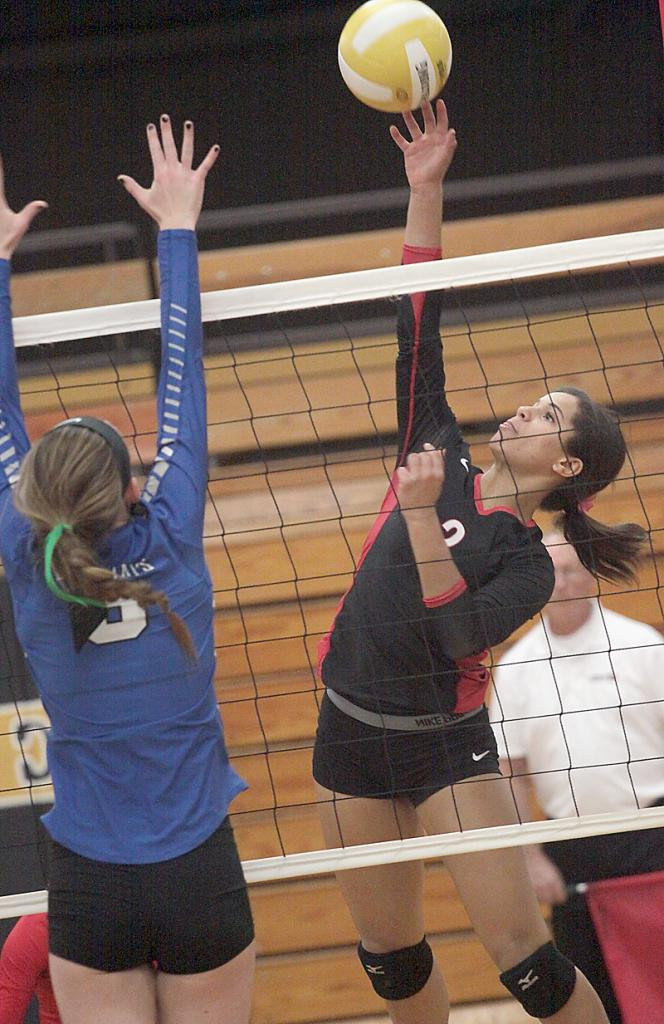 HCHS junior Brenda Hopkins reaches to tip the ball over a Bondurant-Farrar blocker