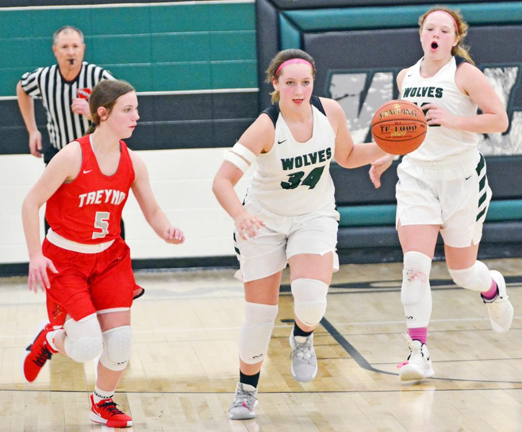 IKM-M junior Bre Muhlbauer (34) advances the ball up the floor for the Wolves as Brooklynn Currin looks on for Treynor. Also pictured for the Wolves is Lexi Branning (right). (Photos by Bob Bjoin)