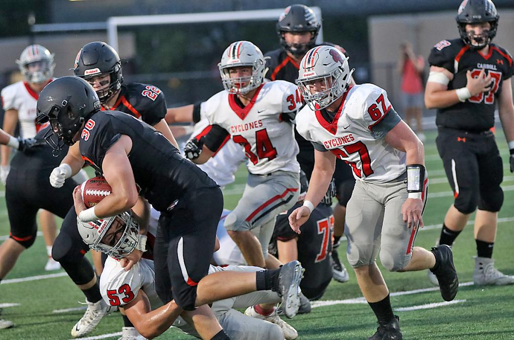 Cyclone defensive end Jacob Schechinger (53) makes the initial hit on Carroll's Ryan Johnston as Jesse Schwery (67) and Jameson Bieker (34) also close in to make the tackle.