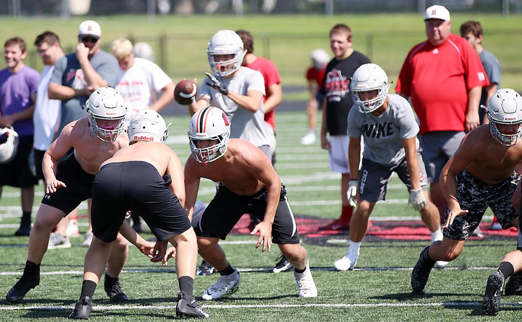 HCHS offensive linemen (left-right) Jesse Schwery, Chandler Leinen and Nathan Henry work on blocking techniques Tuesday as quarterback Johnathan Monson takes a snap.