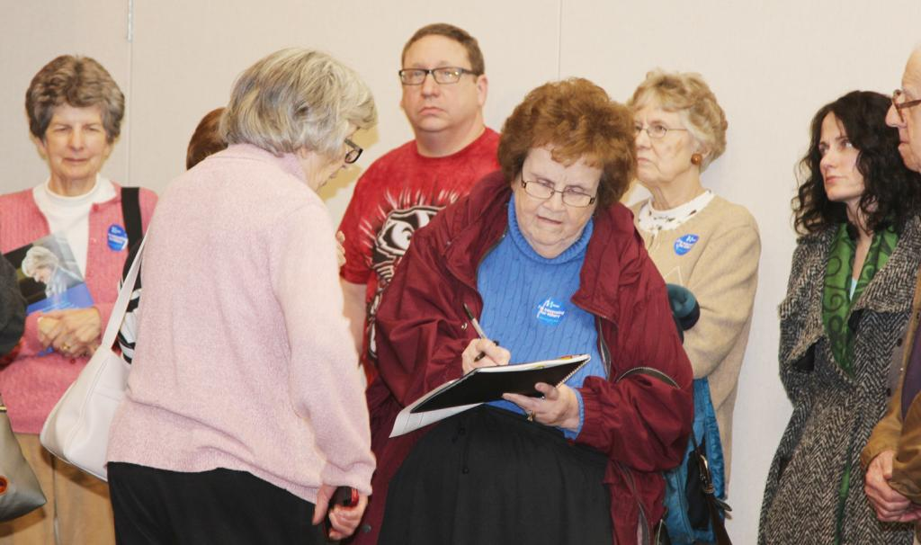 Mary Jensen writes down delegate names at the Democratic caucus site.