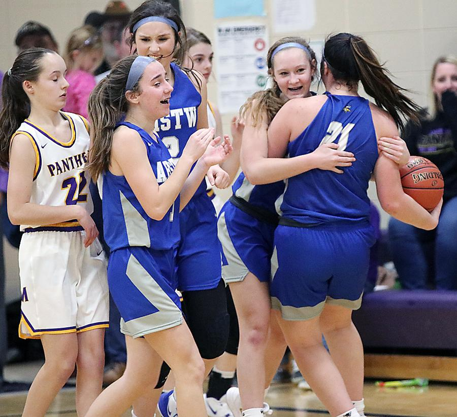 AHSTW senior Kinsey Scheffler (holding basketball) hugs Claire Harris following the Lady Vikes' 48-45 win at Logan-Magnolia. Also pictured for AHSTW are Julia Kock (foreground) and Kailey Jones. (Photos by Mike Oeffner)