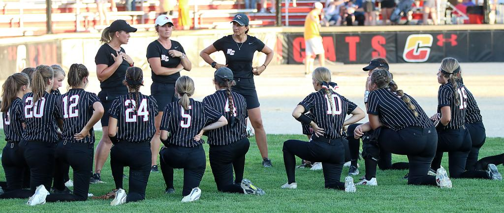 Harlan Community head softball coach Toshia Kasperbauer (left) talks with the Cyclones following Tuesday's 12-0 regional final loss at top-ranked Carlisle. Standing with Kasperbauer are assistant coaches Brandi Eckles (center) and Ann Heithoff. (Photos by Mike Oeffner)
