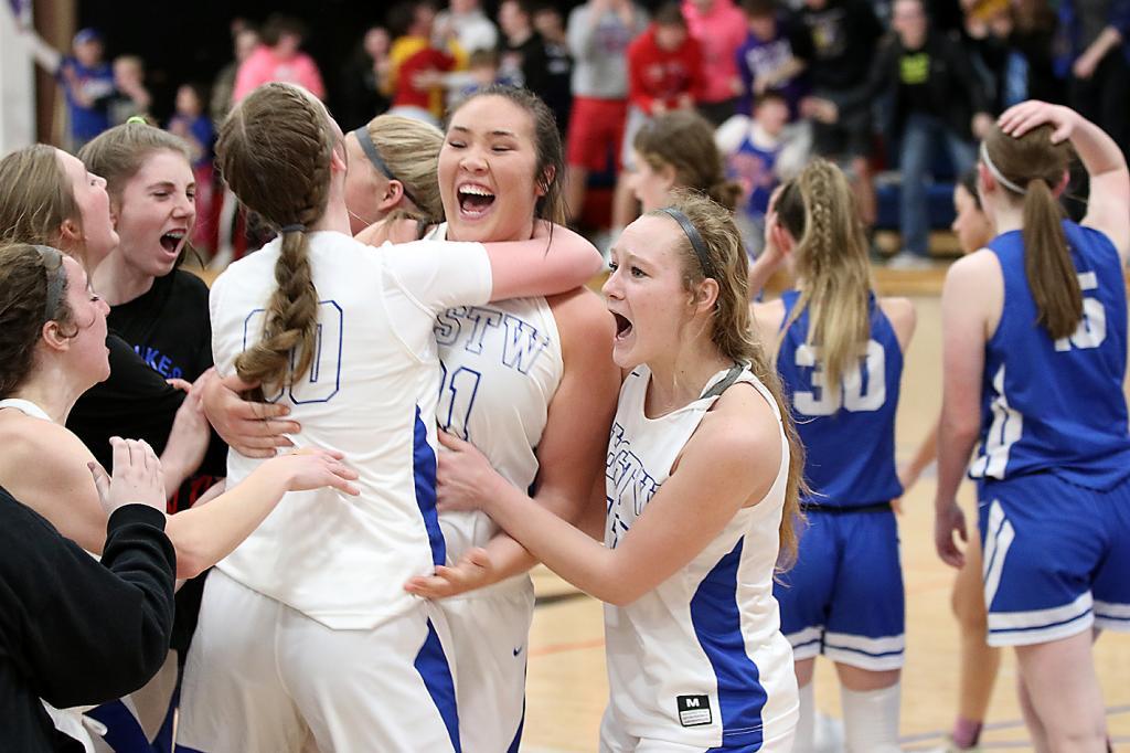 The AHSTW girls basketball team celebrates its thrilling 52-50 regional quarterfinal win vs. Underwood. (Photos by Mike Oeffner)