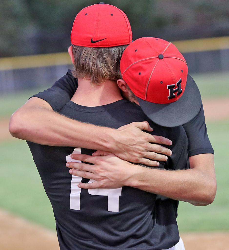 HCHS senior Kobe Livengood hugs sophomore Alex Monson (14) after the Cyclones lost a 12-2 decision in six innings at DC-G.