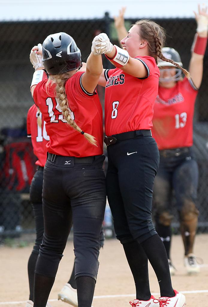Harlan Community juniors Kate Heithoff (8) and Jordan Heese (15) celebrate Heese's walk-off RBI single that gave the Cyclones a 2-1, eight-inning victory over Lewis Central. (Photos by Mike Oeffner)