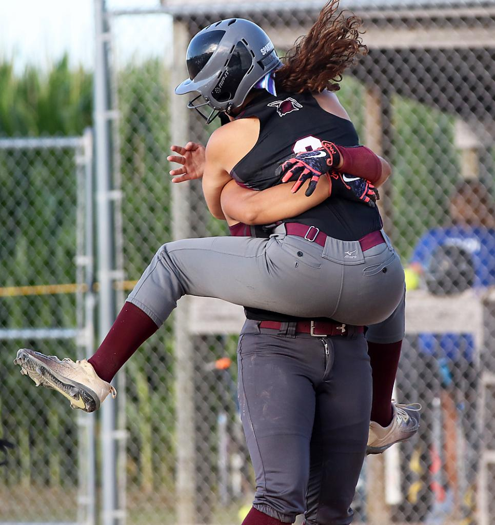 Spartan senior Lexi Madsen leaps into the arms of Tatum Grubbs after scoring the winning run in the team's 5-4 regional win over Griswold. (Photos by Mike Oeffner)