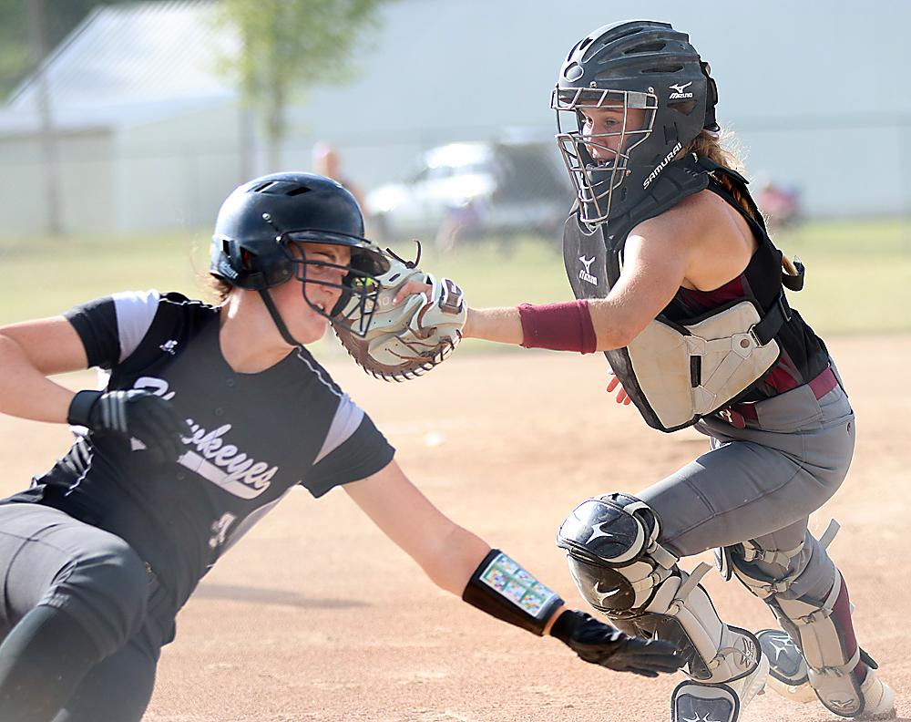 Exira-EHK catcher Quinn Grubbs (right) looks to tag out West Harrison's Sabrina Rife on a fifth-inning play at the plate. Rife was called safe but the 9th-ranked Spartans defeated the Hawkeyes 6-2 to earn a spot in the regional finals. (Photos by Mike Oeffner)
