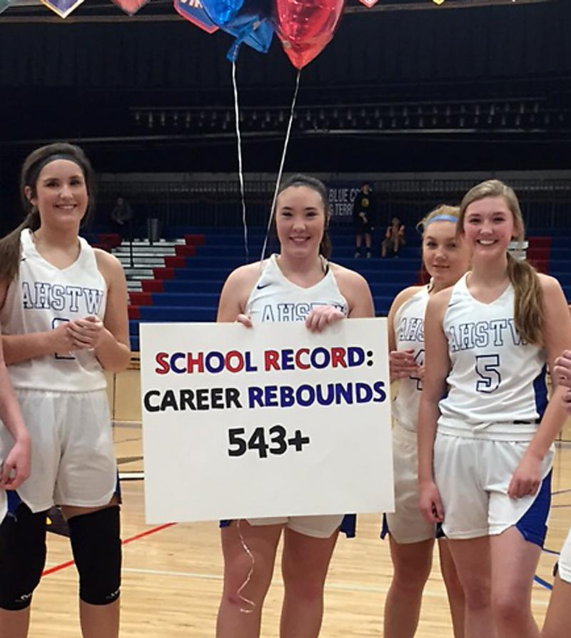 AHSTW senior Kinsey Scheffler received a sign and balloons in recognition of breaking the school record for career rebounds earlier this season. Standing with Scheffler are teammates Kailey Jones (left), Tristin Heiny (5) and Madison Heiny. (Photo contributed)