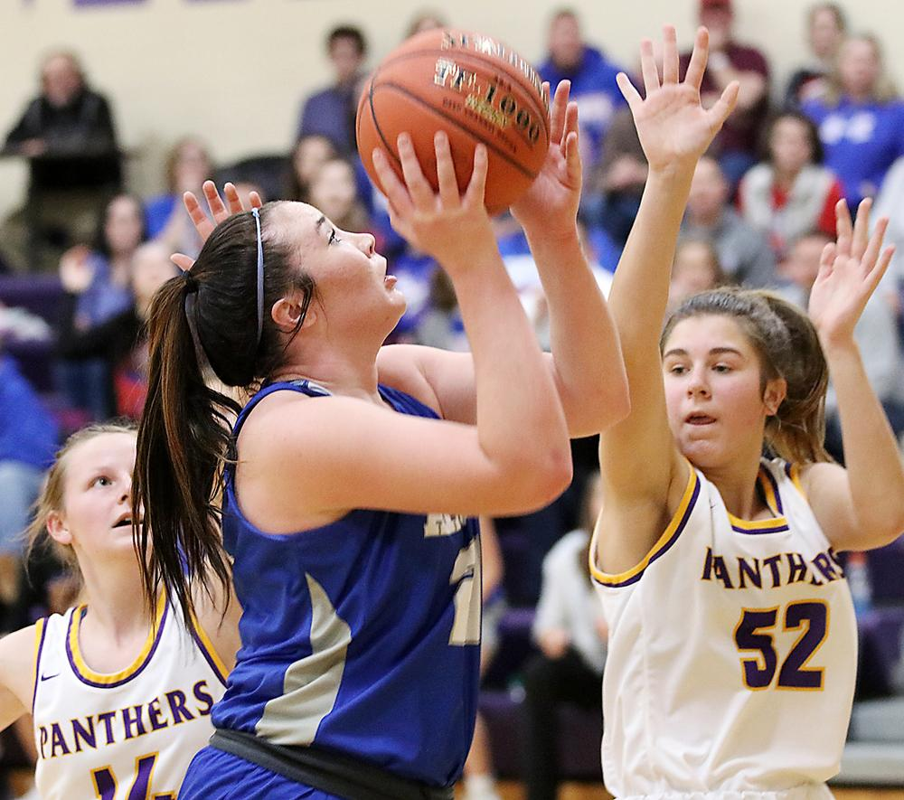Kinsey Scheffler of AHSTW (center) scored a pivotal three-point play on this shot in the lane over Logan-Magnolia's Mya Moss.