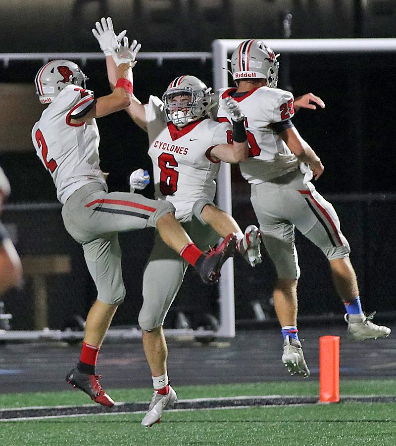 Connor Frame (2), Aidan Hall (6) and Brenden Bartley (25) celebrate Frame's 55-yard touchdown pass to Hall with :37 left in the first half.