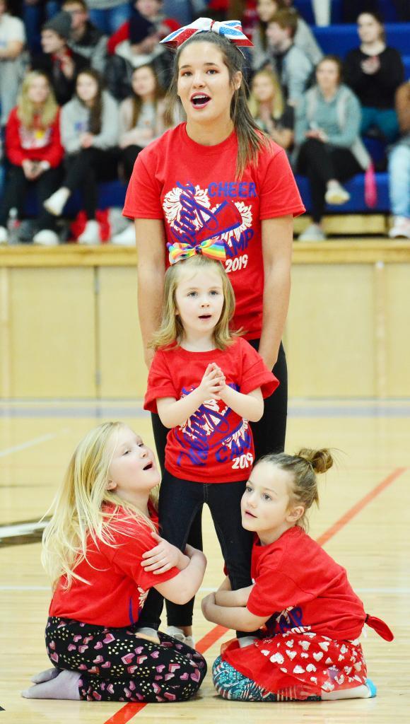 Cheerleader Liz Cordes with Little Cheerleaders L to R -- Brynnleigh Lane, Hadlee Busch and Penelope Rold.