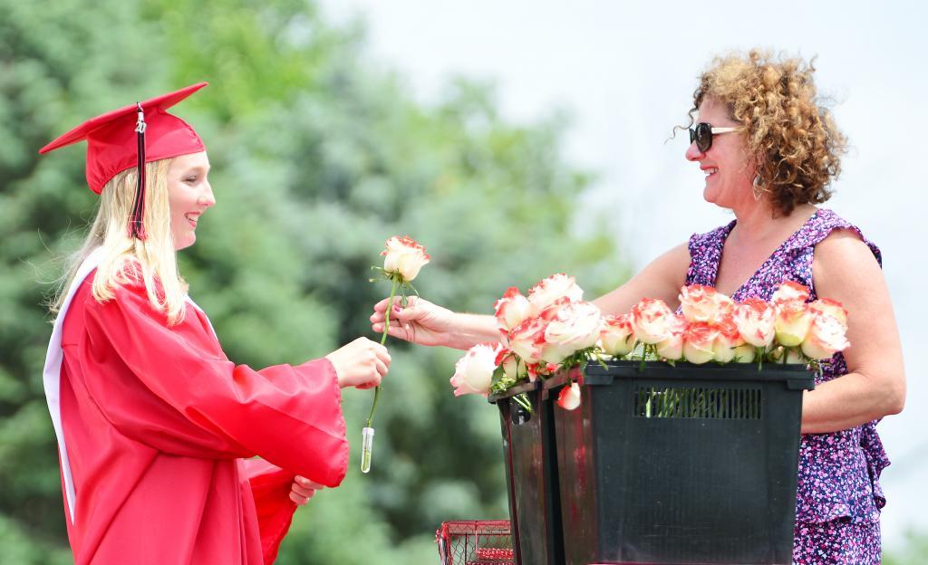Justina Borgman receives a rose from HCS Superintendent of Schools Lynn Johnson.