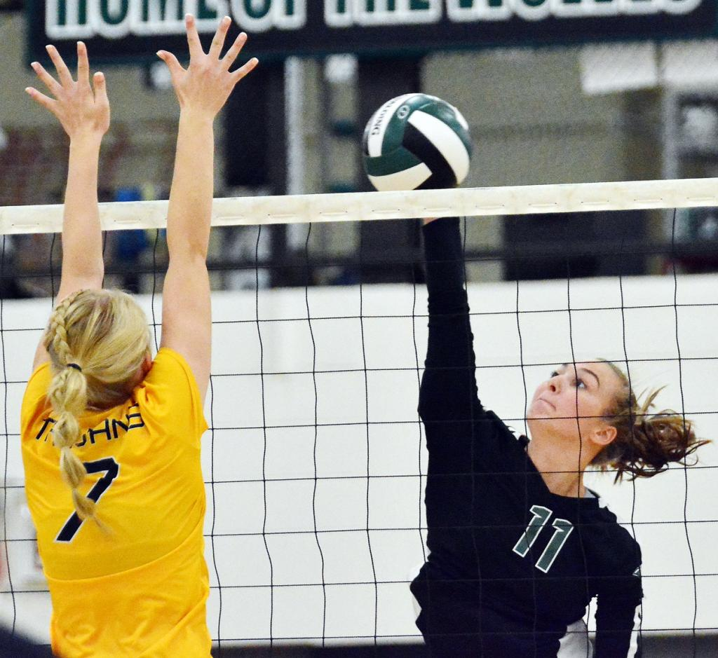 IKM-M junior Kylie Powers (11) goes on the attack as Trojan junior Preslie Arbaugh defends the net. (Photos by Bob Bjoin)