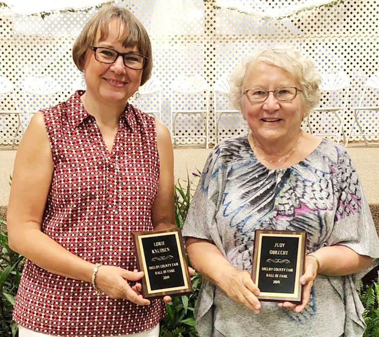 Shelby County Fair Board President Justin Ahrenholtz presents the Hall of Fame award to this year's inductees Judy Obrecht (right) and Lorie Knudsen.  (Photo courtesy Susan Jensen)