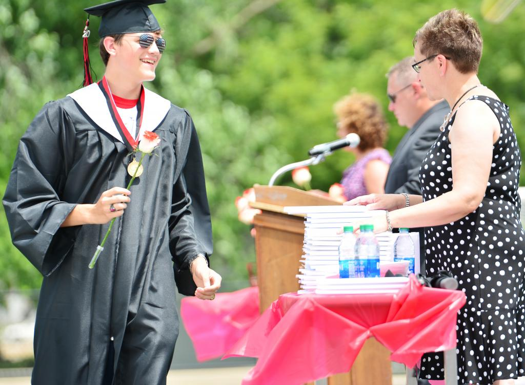 Aaron Porter receives his diploma from HCS Board President Amy Rueschenberg.