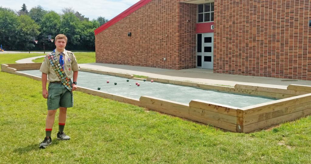 Griffin Schleimer with his Eagle Scout project, a full-size bocce court at the Harlan Community Schools Elementary building.  (Photo contributed)