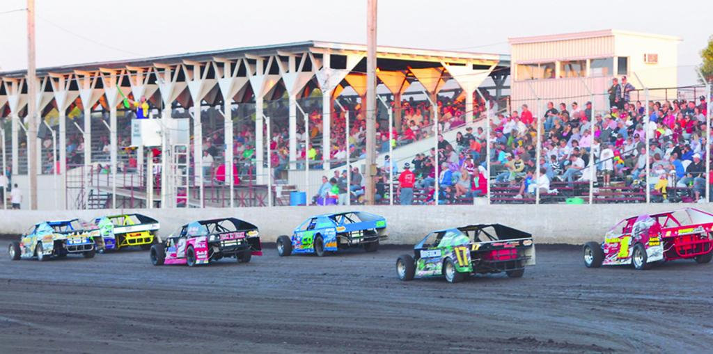 A class of Modifieds races past the grandstand on a green flag during a night of racing at the Shelby County Speedway. The Harlan race track is hopeful to open its 2020 season in the near future when the state will allow fans to attend. (Photo contributed)