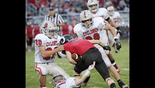 HCHS linebacker Jacob Bartley (28) pulls down Greene County receiver Lance Hughes for an open field tackle as Cyclones Caleb Bieker (38) and Tanner Fink also converge on the ball carrier.