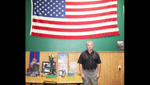 Harlan native and Vietnam War veteran Bill Reid poses by an American flag inside of Wild Willie's, the saloon Reid and his brother-in-law built in 2005. Reid spent 21 years in military service both in the Marines and the Army reserve.