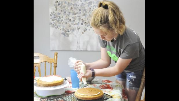 HARLAN -- Mallory Mulligan is one of the 4-H'ers participating in the first 4-H cake decorating competition. Here she is practicing icing the cake.