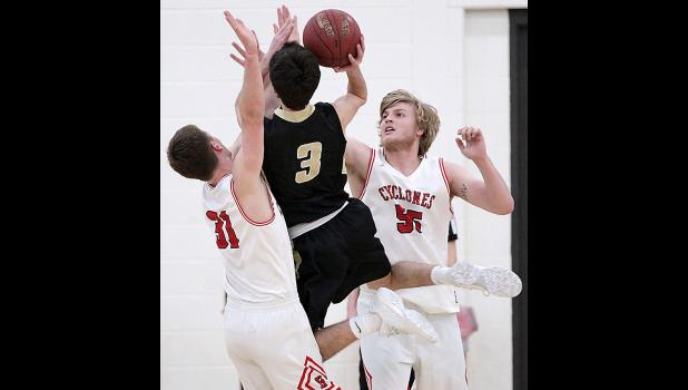 Glenwood's Nate Mohr (3) draws contact on a drive to the basket Friday night as Shane Chamberlain (left) and Jacob Hansen defend for the Cyclones.