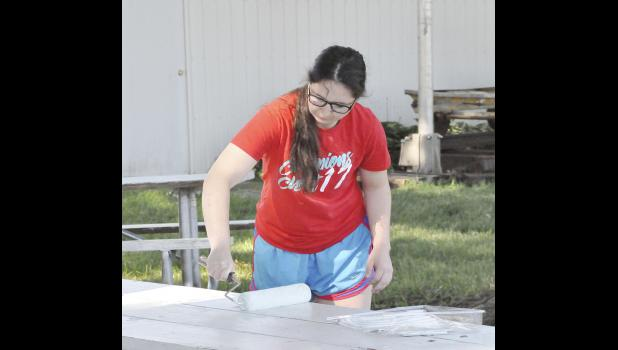 Mikala Kenkel painting picnic tables.